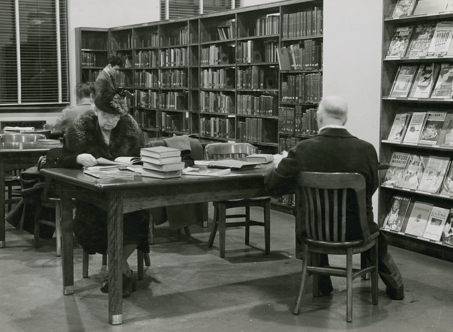 Woman wearing hat and coat with fur collar reads at a table in the London Ontario public library.