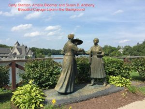 Photo of 1999 statue of the meeting between Stanton, Bloomer and Anthony with Cayuga Lake in the background